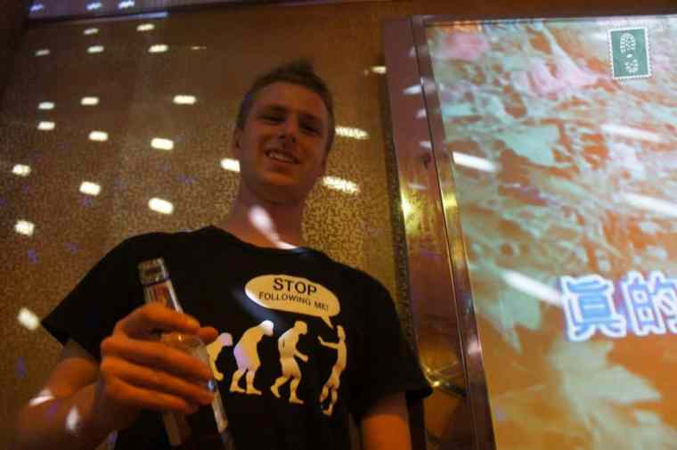 A boy holding a beer in hands in Chinese KTV