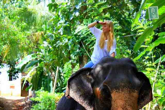 A girl is riding an elephant