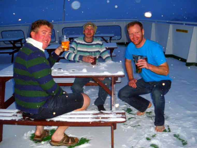 Three guys are enjoying the cold beer at Antarctica