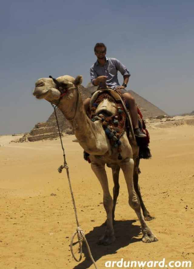 A guy is riding a camel in Egypt