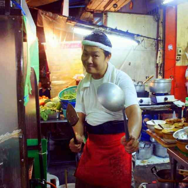 A Thai cook is holding cooking equipment