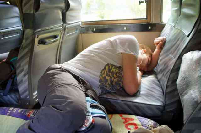 A boy is sleeping on the bus