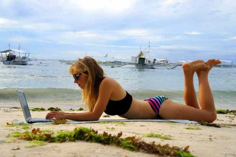 A girl blogging on the beach