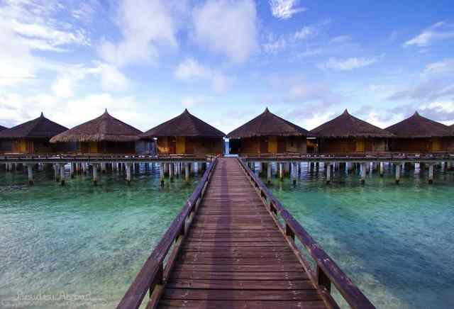 Luxurious overwater villas line the jetty along the bright blue shore
