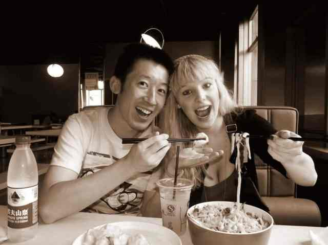 A girl and Chinese boy are eating