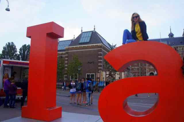 A girl on top of Iamsterdam sign
