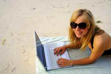 Agness writing a blog post on the beach