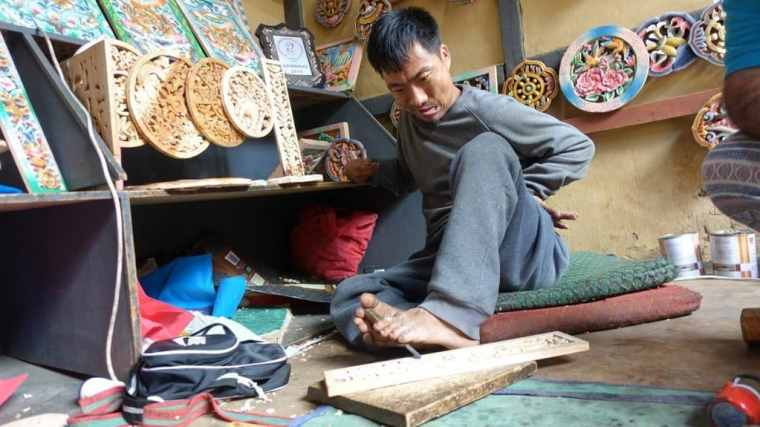 A man carving wooden crafts with his feet on Bhutan tour itinerary