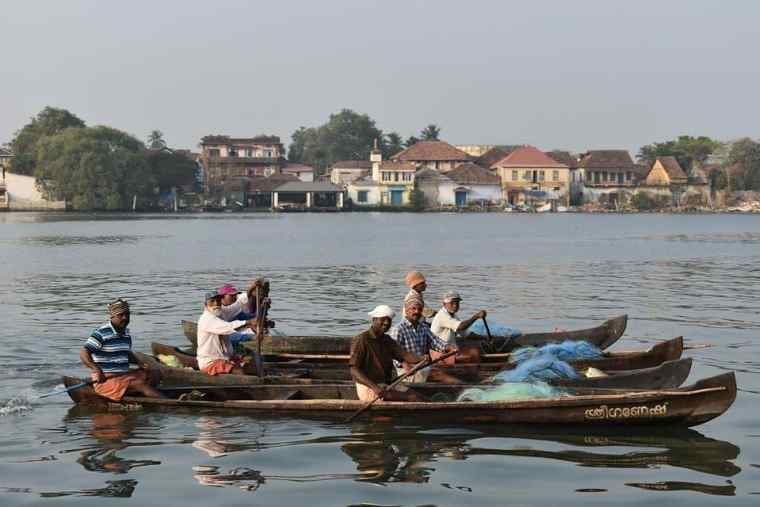 Men on boats by Fort Kochi