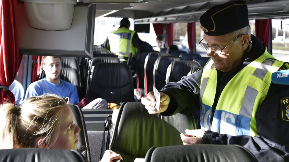 A Swedish border guard checking documents