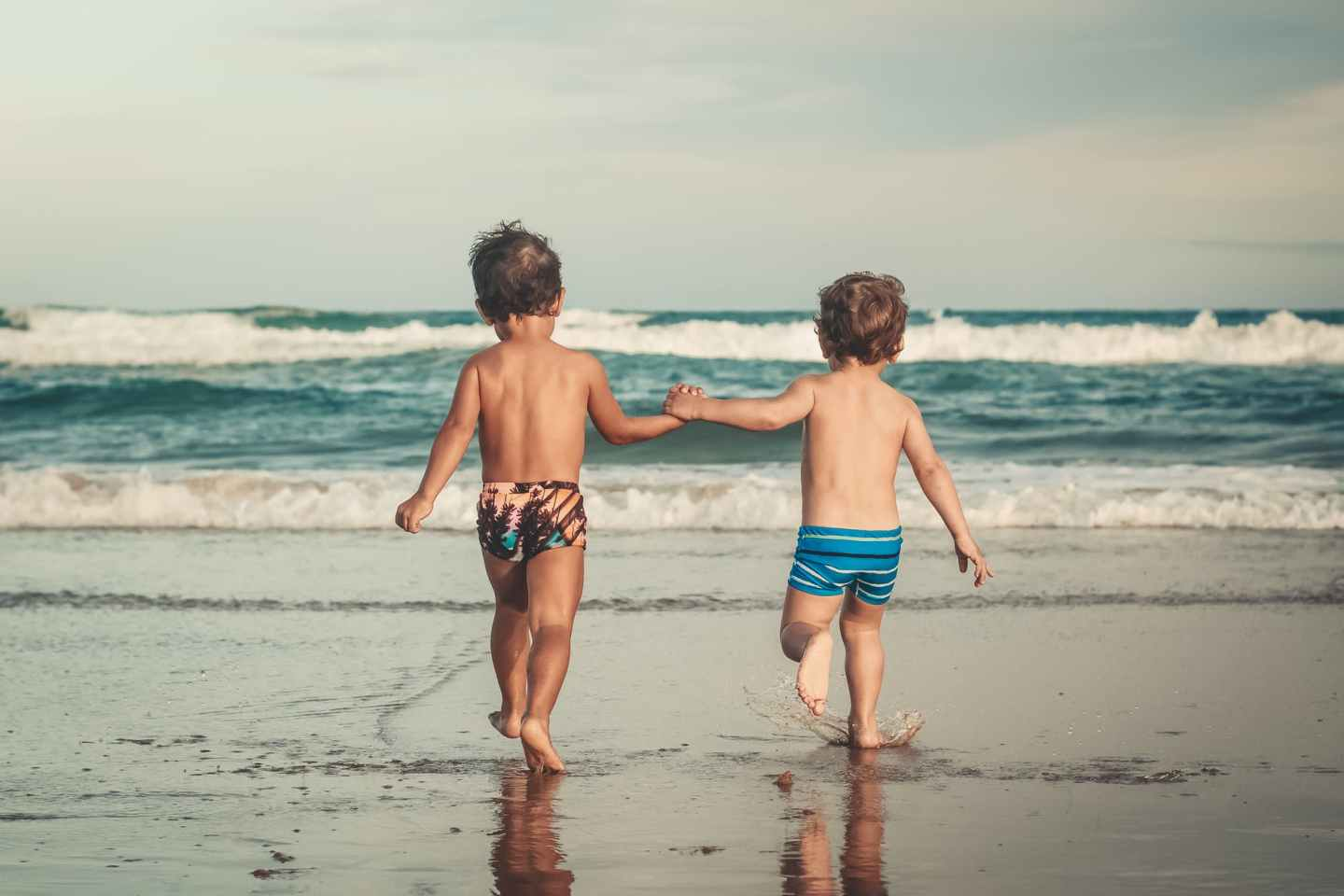 unrecognizable little boys holding hands and walking on sandy seashore