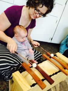 Baby plays xylophone at Little Notes Baby Music Class Eugene