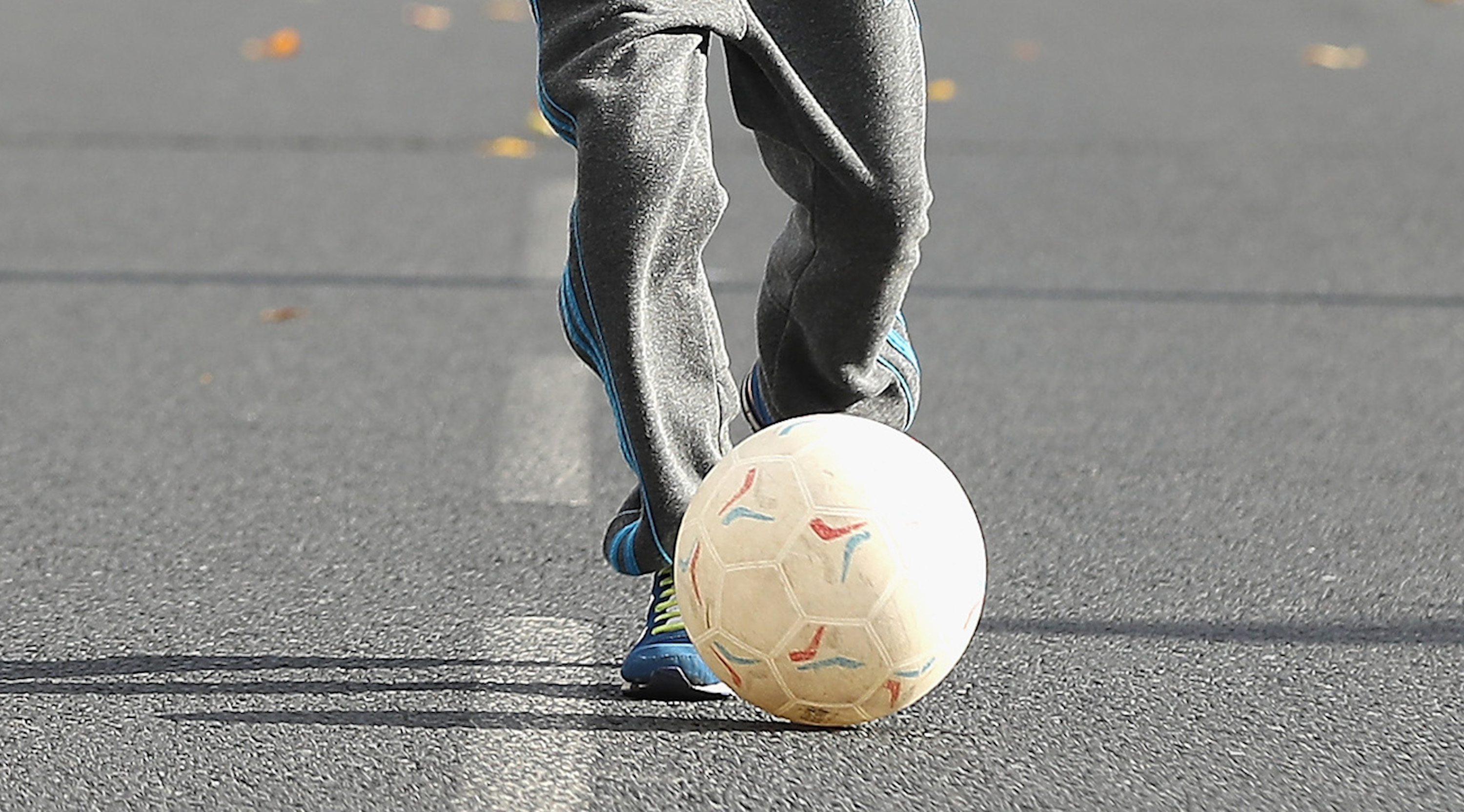 BURNLEY, ENGLAND - OCTOBER 22: A young Burnley fan plays football in a near by street during the Premier League match between Burnley and Everton at Turf Moor on October 22, 2016 in Burnley, England. (Photo by Chris Brunskill/Getty Images)