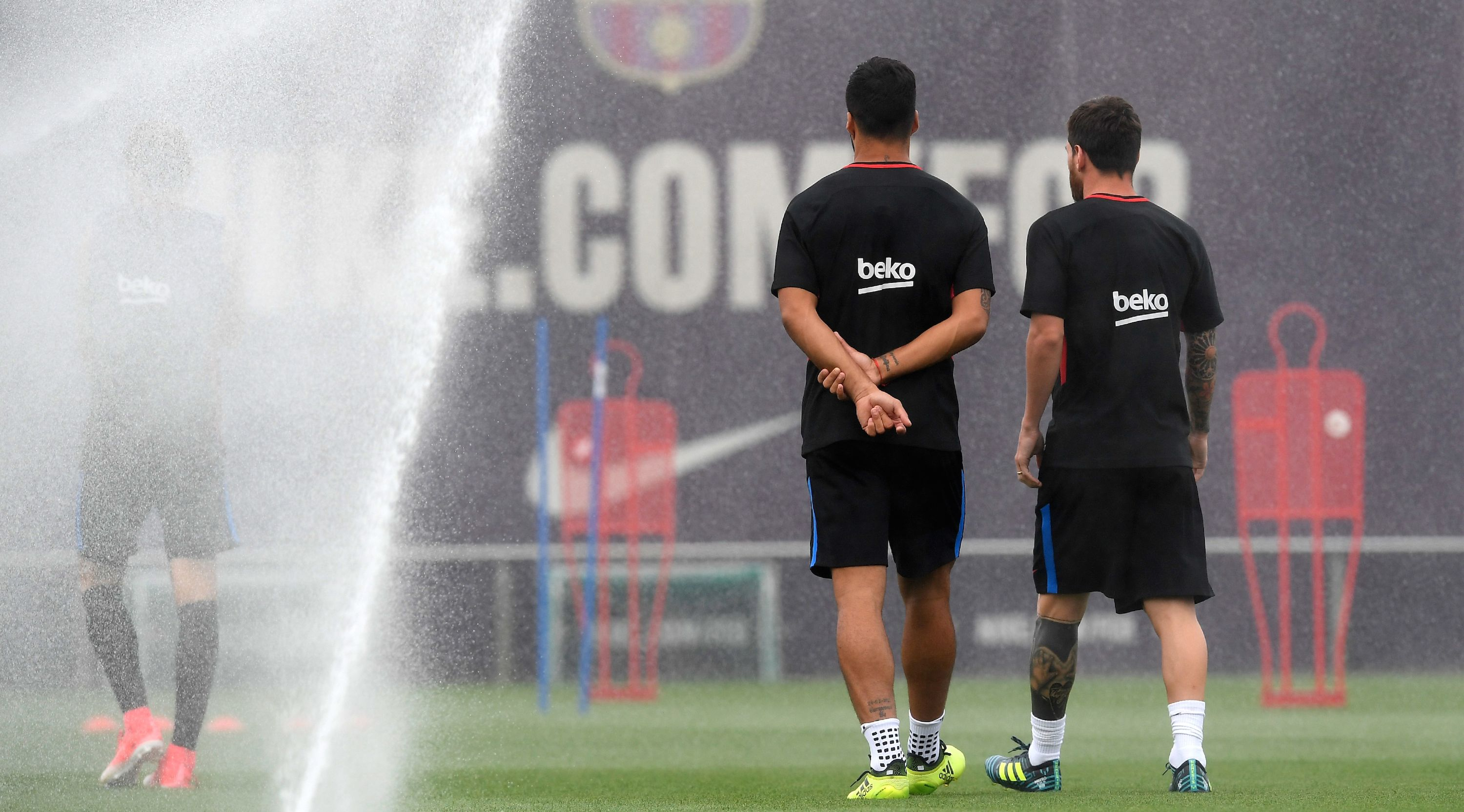 Barcelona's Argentinian forward Lionel Messi (R) talks with Barcelona's Uruguayan forward Luis Suarez (L) during a training session at the Sports Center FC Barcelona Joan Gamper in Sant Joan Despi, near Barcelona on August 15, 2017, on the eve of the Spanish Supercup second leg football match Real Madrid vs FC Barcelona. / AFP PHOTO / LLUIS GENE (Photo credit should read LLUIS GENE/AFP/Getty Images)
