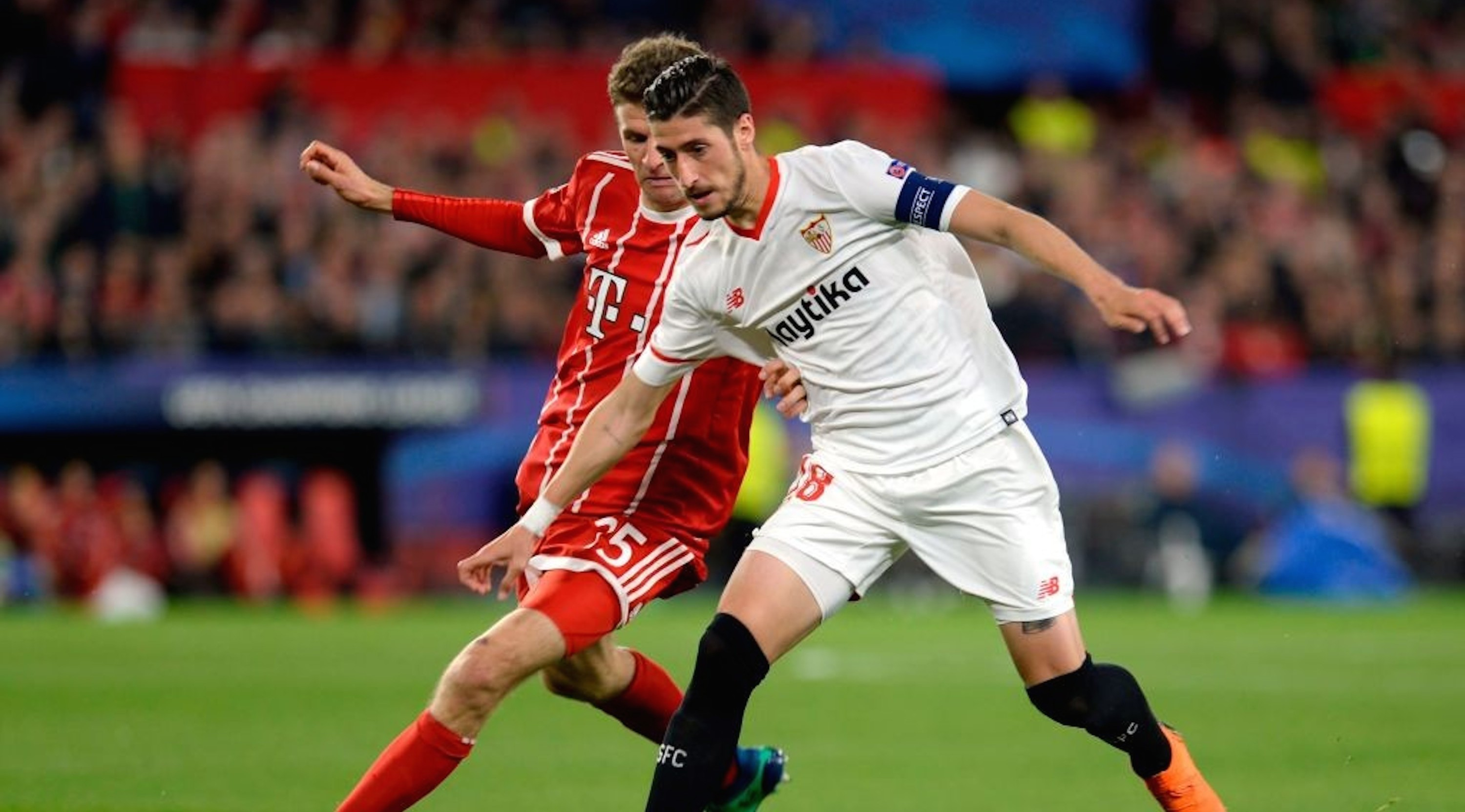 Bayern Munich's German forward Thomas Mueller (L) vies with Sevilla's Spanish defender Sergio Escudero during the UEFA Champions League quarter-final first leg football match between Sevilla FC and Bayern Munich at the Ramon Sanchez Pizjuan Stadium in Sevilla on April 3, 2018. / AFP PHOTO / CRISTINA QUICLER (Photo credit should read CRISTINA QUICLER/AFP/Getty Images)