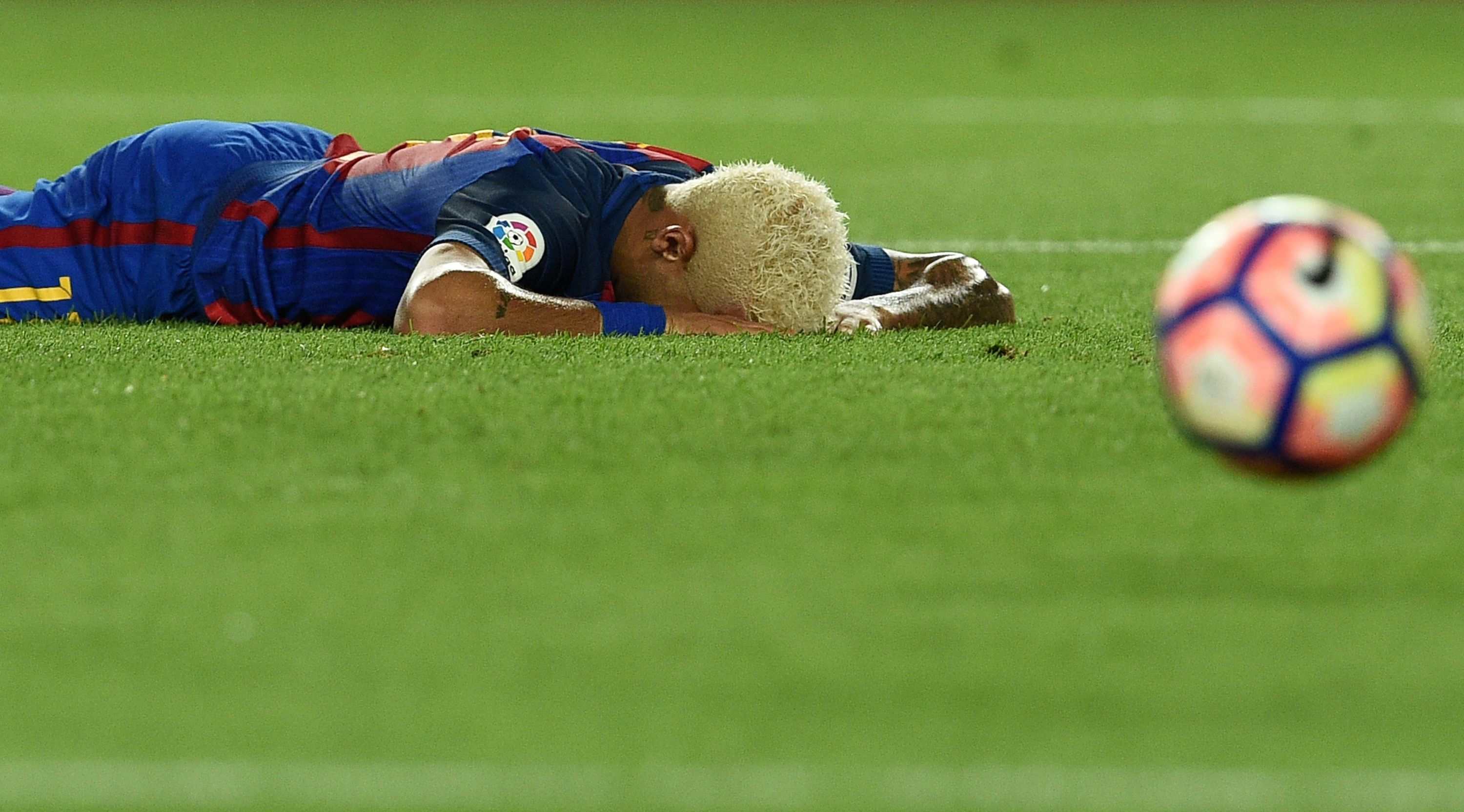 Barcelona's Brazilian forward Neymar lies on the pitch after missing a goal during the Spanish league football match FC Barcelona vs Deportivo Alaves at the Camp Nou stadium in Barcelona on September 10, 2016. / AFP / LLUIS GENE (Photo credit should read LLUIS GENE/AFP/Getty Images)