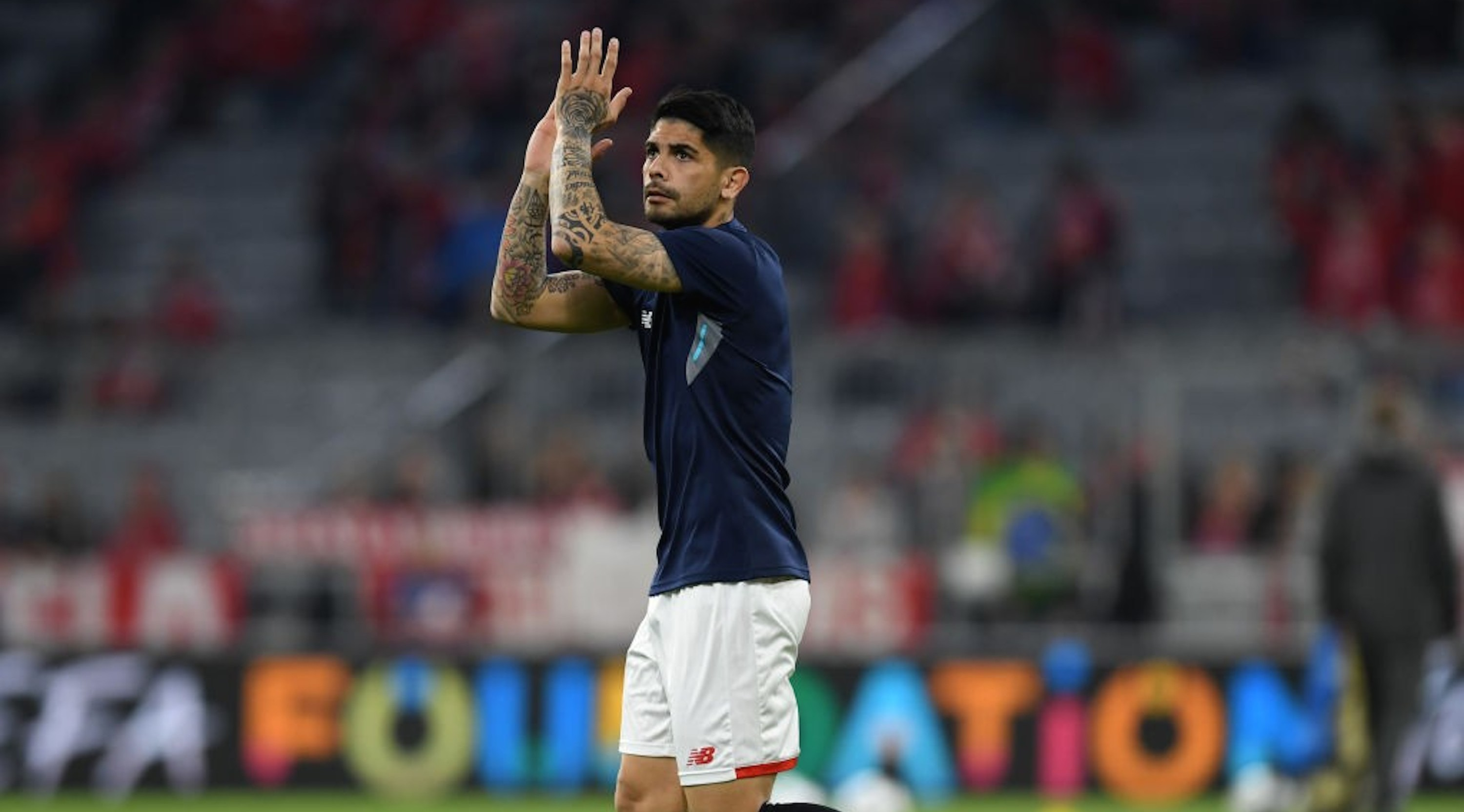 Sevilla's Argentinian midfielder Ever Banega applauds prior to the UEFA Champions League quarter-final second leg football match between FC Bayern Munich and Sevilla FC on April 11, 2018 in Munich, southern Germany. Bayern Munich marched into another Champions League semi-final despite 10-man Sevilla holding them to a goalless draw at home. / AFP PHOTO / Christof STACHE (Photo credit should read CHRISTOF STACHE/AFP/Getty Images)