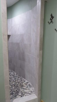 The bathroom has a very large walk-in shower with a flat pebble rock tile floor. No hitting your elbows here!