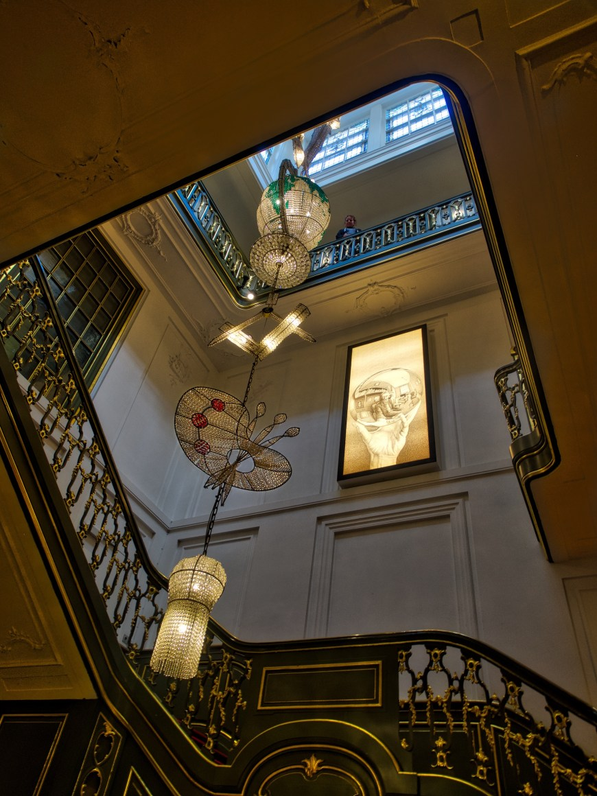 Escher stairwell; royally decorated stairs; strikingly illuminated by the chandeliers.