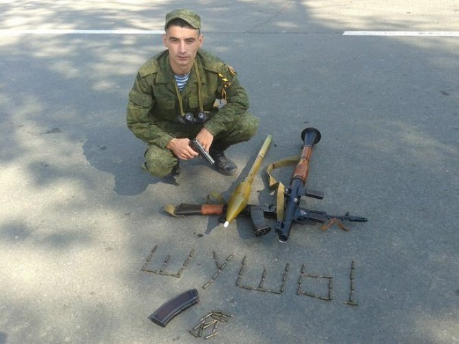 "Gritsyuk posing with weapons, spelling out """" with bullets"