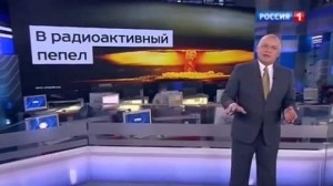 """Dmitry Kiselyov and image of nuclear mushroom cloud, boasting Russia's ability to turn US """"Into Radioactive Dust."""" Dmitry Kiselyov is the head of the Kremlin's RT (Russia Today) news agency, a soapbox to promote the Kremlin's policies, denigrate the West and speculate about Western-led conspiracies as well as attack the political opposition to Putin. (Image: screen capture)"""
