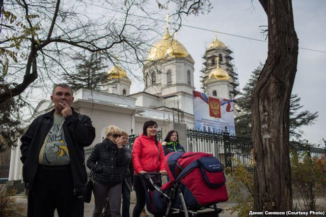 Krimbewohner vor der St. Peter und Paul Kathedrale in Simferopol, an der ein Plakat hängt, das besagt, dass Wladimir Putin persönlich die Schirmherrschaft für die Restaurierung der Kirche übernommen hat.
