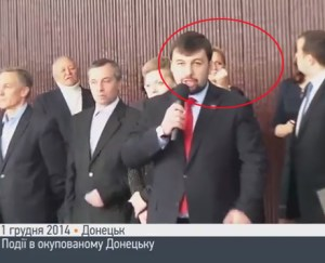Woman behind speaking Pushilin threaten the youth with her fist