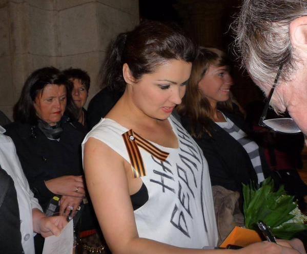 """Anna Netrebko mit dem St.-Georgs-Bändchen (ursprünglich von der russischen Wlassow-Armee benutzt"""" und der Aufschrift """"Nach Berlin"""" auf der Brust"""