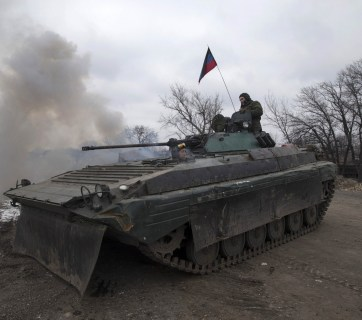 Fighters with the separatist self-proclaimed Donetsk People's Republic army sit on top of a moving armoured personnel carrier at a check point on the road from the town of Vuhlehirsk to Debaltseve