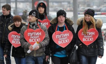 "Russian youths wearing signs ""Putin loves everyone!"" (Photo: nr2.com.ua)"