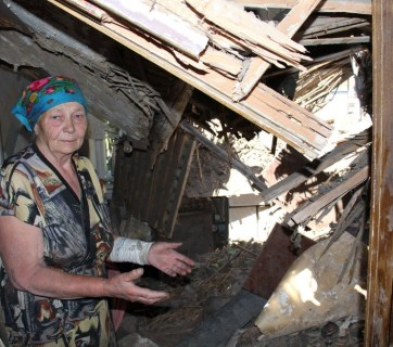 A wounded resident of the Ukrainian town of Maryinka showing her house destroyed as a result of the tank attack and bombardment by Russian heavy artillery and multiple launch missile systems in violation of Minsk-2 Accords, June 2015 (Image: 112.ua)