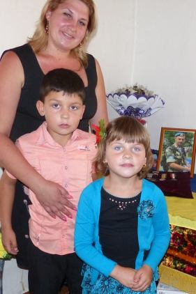 Maryna with her two children standing at a memorial to her husband Oleksandr, including a few pictures and his commendation for bravery.
