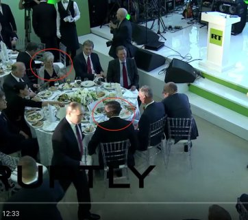 "Former national security advisor, former Director of US Defense Intelligence Agency, retired Lieutenant General Mike Flynn at a conference and gala dinner celebrating the 10th anniversary of Russia's propaganda arm, media channel ""RT"" (formerly ""Russia Today"") seated at the head table at the gala, with Vladimir Putin, his then-chief of staff, Sergei Ivanov and press spokesman Dmitry Peskov, among other Russian officials. Also seated at the same table is 2016 Green Party candidate for president Dr. Jill Stein. December 10, 2015 in Moscow. (Image: video capture)"