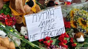 "Flowers left near the Dutch embassy in Kyiv, Ukraine for victims of Malaysia Airlines MH17. The note says in Russian: ""Putin, the world will not forgive you."""