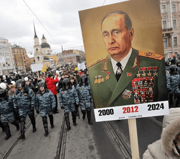 Surrounded by riot police, demonstrators in St. Petersburg carry a poster depicting Prime Minister Vladimir Putin as the elderly Soviet Communists party leader Leonid Brezhnev in February 2012, with less than a week remaining before he was elected as Russian President for the third time (Image: EPA)