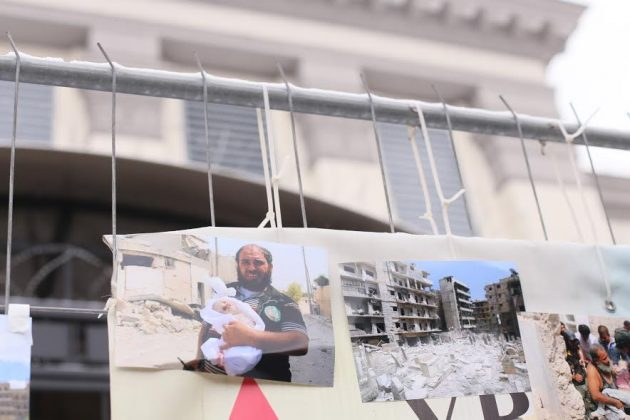 Photos of destroyed Syria were taped over the fence of the embassy. Photo: