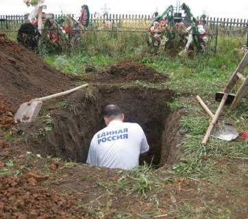 "The grave digger wearing a t-shirt of Russia's ruling party ""United Russia."" (Image: social media)"