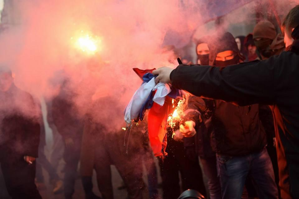 """Right sector activists and other national organizations burn a Russian flag after vandalizing the office of """"Rossotrudnichestvo"""" (Russia's agency for the Commonwealth of Independent States, Compatriots Living Abroad and International Humanitarian Cooperation) on 17 February 2018. Photo: pravyysektor.info"""