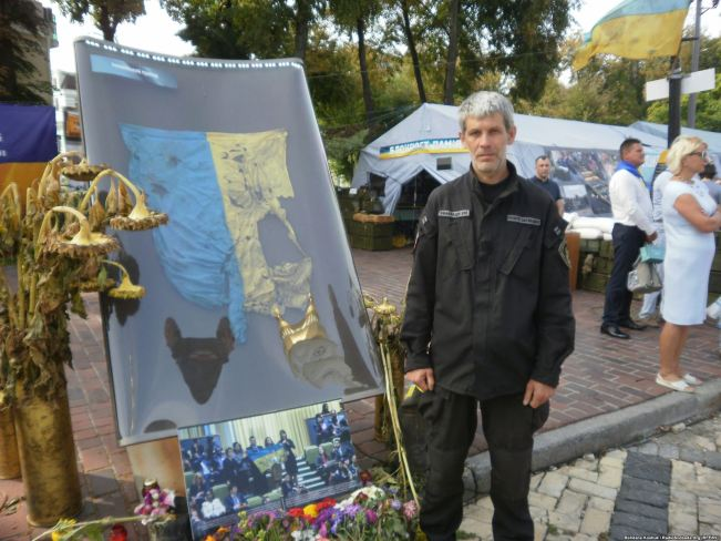 Vadym Mashtabey with battered Ukrainian flag from Donetsk Airport - at the exhibition Checkpoint of Remembrance