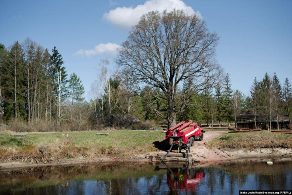 Firefighters replenish their water supply in a pond near the village of Vystupovichi