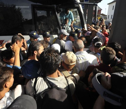 Migrants boarding a coach at Beli Manastir station near the Hungarian border, Croatia