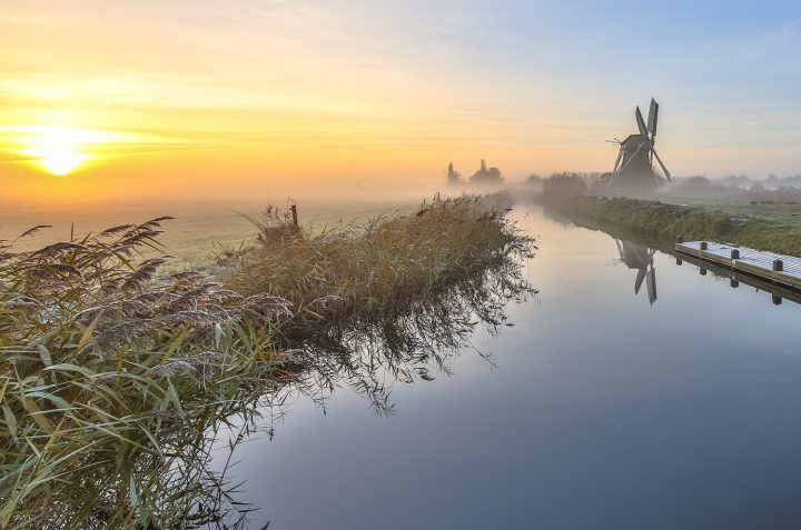 Romantic Dutch countryside in winter - typical polder with a windmill