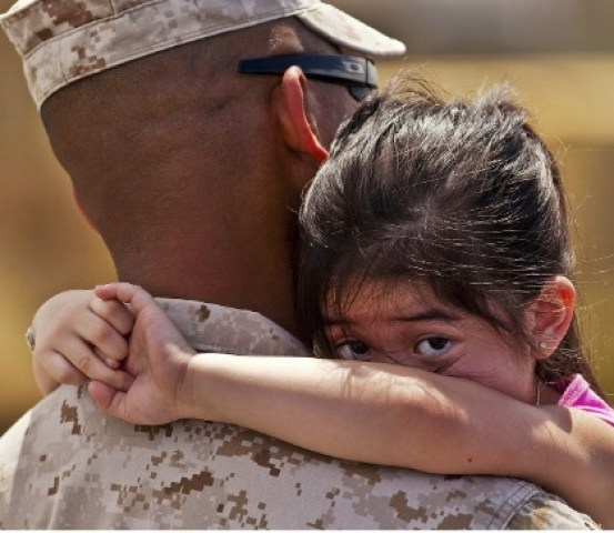 Military vet holds a child canva