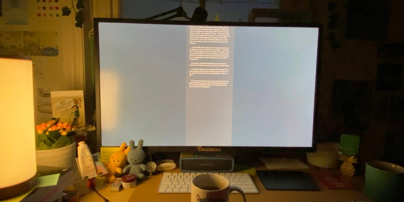 Desk with big monitor, lit from the left. A mug sits in front of the keyboard.