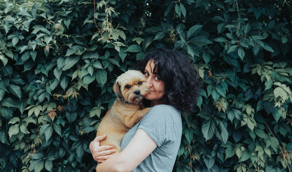 woman posing with her small dog in front of a hedge
