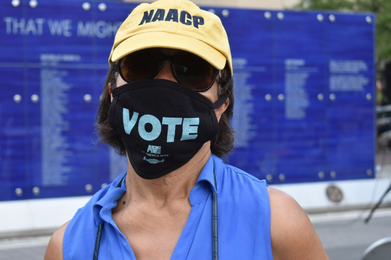 Gerri Sizemore wearing a black face mask with the word VOTE on it, an NAACP baseball cap, and sunglasses