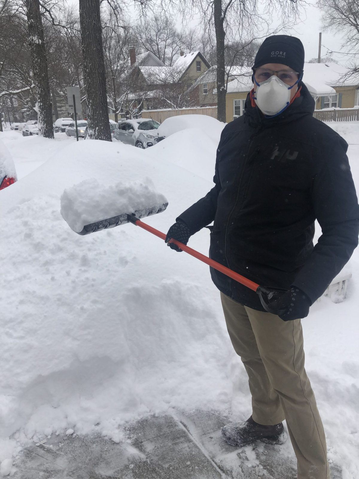 Michael Girard wearing a mask while shoveling snow