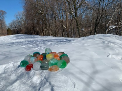 A pile of colorful frozen balloon orbs decorate a snowy hillside on a bright, clear day