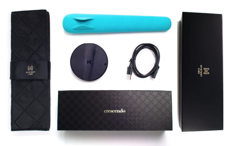 Image description: A layout of all the items in the Mysteryvibe Cresendo box. In the centre the teal Cresendo, below that the round charging dock, and the cable. Blow that there's the black box with gold lettering. The left hand side has the carry case, and the right the outside box.