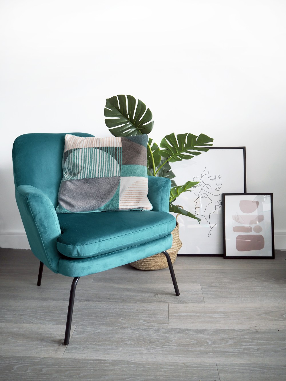 Teal velvet armchair with a plant and some abstract art prints